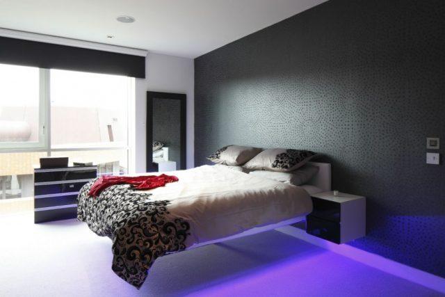 Тёмные обои и парящая кровать – два зрительных акцента этой спальни